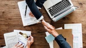 Ordenador,apretón de manos entre dos personas y otra persona redactando documentos