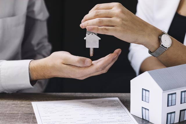 manos entregando las llaves de una casa