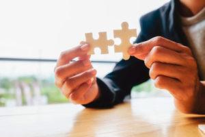 manos uniendo piezas de puzzle